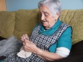 picture of elderly  - Elderly woman sewing in her home - JPG