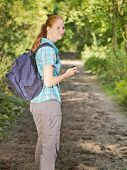 stock photo of gps navigation  - Young female hiker checks surroundings while navigating with a GPS navigation system on a path in a green summer forest - JPG