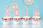 foto of red velvet cake  - Happy New Year for 2015 red velvet cupcakes in red and white theme with lit candles and and snowflake decorations on pale blue and white background - JPG