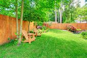 stock photo of lawn chair  - Fenced backyard with green lawn flower beds and romantic sitting area with wooden chairs and table - JPG
