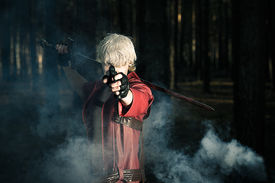 image of gunshot  - man with a sword and a gun in the hands of a smoky the forest - JPG