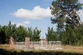 stock photo of burial  - Detail of section of an old cemetary with fenced burial plot - JPG