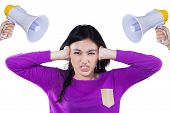 picture of school bullying  - Teenage girl close her ears when bullied with two megaphone isolated on white - JPG
