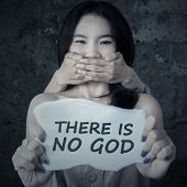 pic of kidnapped  - Teenage girl violence victim and kidnapping showing a paper with a text THERE IS NO GOD - JPG