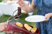 picture of frazzled  - Woman refusing frazzled sausage on barbecue party - JPG