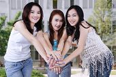 foto of joining hands  - Attractive teenage girls smiling on the camera while joining hands at school yard - JPG