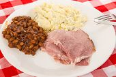 stock photo of baked potato  - Sliced ham on white plate with Brown Sugar and molasses baked beans and potato salad on red plaid country kitchen tablecloth - JPG