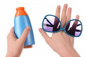 image of suntanning  - Bottle of suntan cream and sunglasses in female hands isolated on white - JPG
