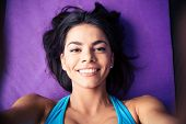 foto of yoga mat  - Closeup portrait of a smiling young woman lying on the yoga mat at gym - JPG