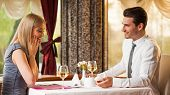stock photo of propose  - Happy couple at restaurant, man is proposing his girlfriend