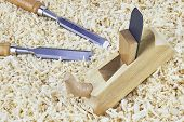 stock photo of chisel  - Two chisels and one spokeshave lying in wooden shavings - JPG