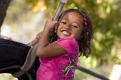 stock photo of tire swing  - Young girl swinging on tire swing on nice fall day