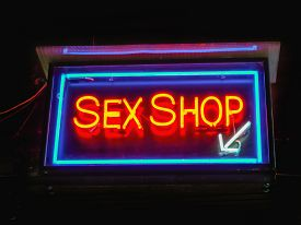 picture of x-rated  - Red neon sex shop sign indicates the entrance at the shop - JPG