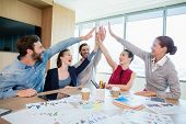 Team of business executives giving high five in conference room at office poster