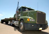 stock photo of big-rig  - Big green diesel truck with empty flatbed photographed under bright noonday sunshine - JPG