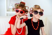 Two funny little girls with curlers in their hair make themselves a make-up. Kids fashion. Family a poster