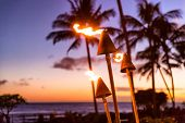 Hawaii sunset with fire torches. Hawaiian icon, lights burning at dusk at beach resort or restaurant poster