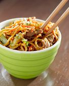 stock photo of lo mein  - eating beef lo mein in a bowl with chopsticks - JPG