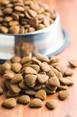 Dry kibble dog food on wooden table. poster
