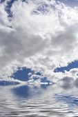 Fluffy clouds in the sky with reflection on water. poster