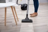 Low Section Of Person Using Vacuum Cleaner For Cleaning Hardwood Floor At Home poster