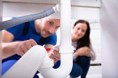 Young Woman Looking At Male Plumber Fixing Sink Pipe In Kitchen poster