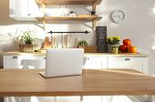 Closeup Of Laptop On Kitchen Counter. Kitchen On Background poster
