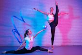 Pretty Two Young Slim Gymnast Women In Sports Clothing Stretching In Front Of Brick Wall In Neon Lig poster