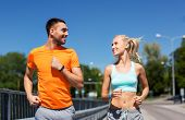 sport, technology and lifestyle concept - happy couple with fitness trackers running along bridge in poster