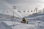Snow Cannon And Ski Lifts On Sunlit Mountain Slope poster