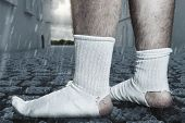 Standing Feet With White Socks And A Big Hole Standing On Cobblestone Street. Concept Homelessness A poster
