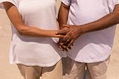 Mid section of senior couple holding hands and standing on beach in the sunshine poster