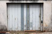 Old Dilapidated Partially Rusted Grey Metal Garage Doors Mounted On Concrete Wall Next To Concrete R poster