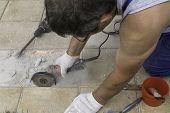 A Circular Saw. A Man Sawing Ceramic Tiles. Worker Sawing A Tile On A Circular Saw. Construction Wor poster