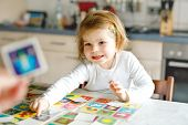 Adorable Cute Toddler Girl Playing Picture Card Game With Mother Or Father. Happy Healthy Child Trai poster