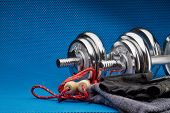 Sport accessories. Steel dumbbells, gloves and skipping rope on a blue background. Fitness, sport an poster
