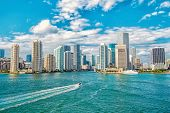 Aerial View Of Miami Skyscrapers With Blue Cloudy Sky, White Boat Sailing Next To Miami Florida Down poster
