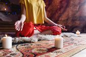 Close-up Of Womans Hand In Yoga Lotus Pose Meditating In A Crafting Room With Candles poster