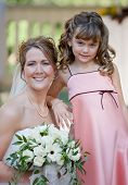 stock photo of flower girl  - Beautiful Bride Posing With Her Flower Girl - JPG