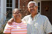 stock photo of senior-citizen  - Senior Minority Couple Standing Outside Their Home - JPG