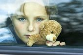stock photo of pain-tree  - Little sad girl is in the car - JPG
