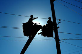 picture of power lines  - silhouette of two linemen working on power and communication lines - JPG