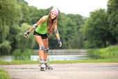 image of inline skating  - Happy young girl enjoying roller skating rollerblading on inline skates sport in park - JPG