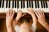 pic of baby toddler  - Closeup portrait of a baby learning to play piano with mother  - JPG