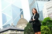 Business woman confident outdoor in Hong Kong standing proud in suit cross-armed in business distric