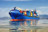 stock photo of logistics  - blue cargo container ship anchored in harbour - JPG