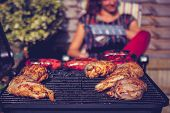 image of raw chicken sausage  - Chicken And Sausages On Barbecue With Woman In Background