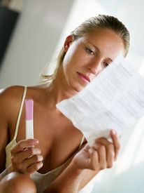 stock photo of pregnancy test  - blonde woman holding pregnancy test and reading information - JPG