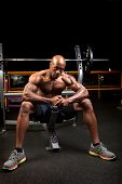 picture of weight lifter  - Weight lifter sitting at the bench press about to lift a barbell - JPG