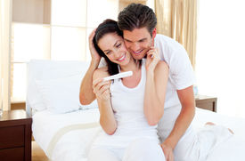 image of pregnancy test  - Enamoured couple finding out results of a pregnancy test sitting on the bed - JPG